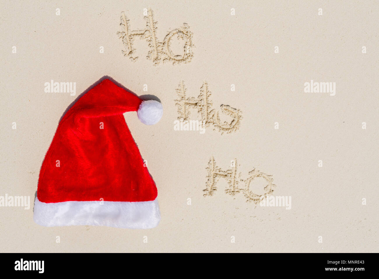 Santa hat on a white sand tropical beach - Stock Image