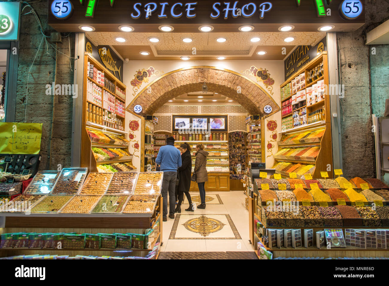 Customers peruse the shelves of a spice shop at Istanbul Spice bazaar in Turkey - Stock Image