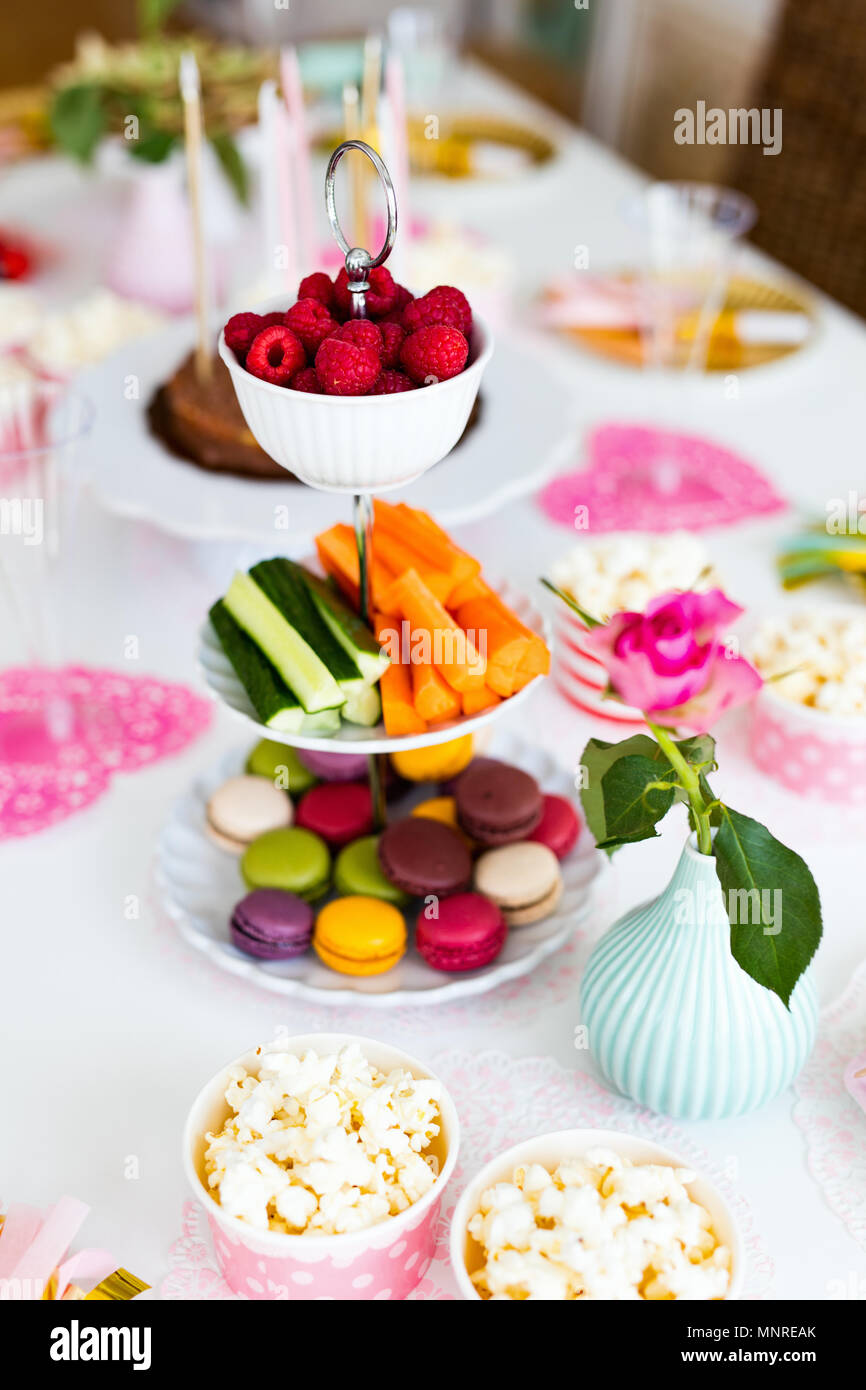 Cake,  candies,  marshmallows,  popcorn,  fruits and other sweets on dessert table at kids birthday party - Stock Image