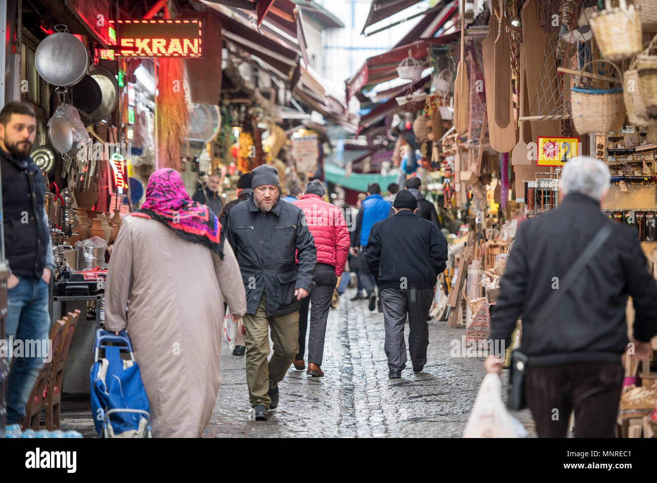 Shoppers walk along busy narrow street of outdoor marketplace selling various goods, Istanbul, Turkey Stock Photo