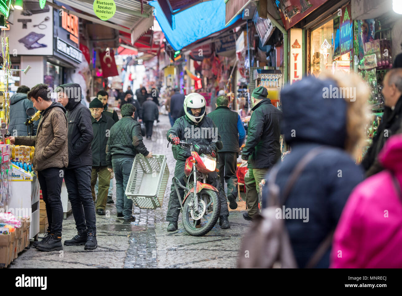 Shoppers browse goods for sale along busy narrow street of outdoor marketplace as a man with a motorcycle tries to make his way through, Istanbul, Tur Stock Photo