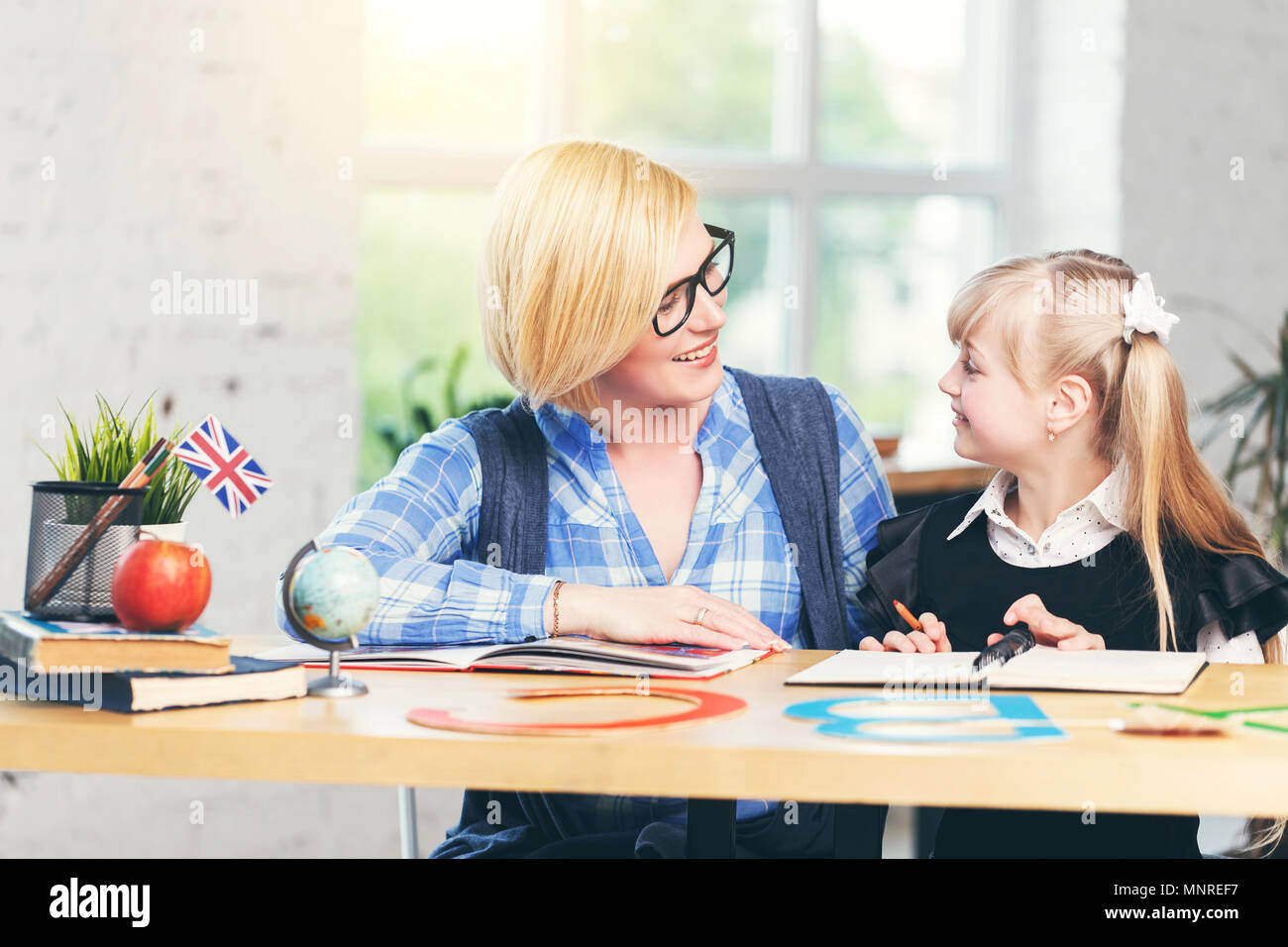 English language female teacher studying with smart kid girl in light white classroom, children learning concept - Stock Image