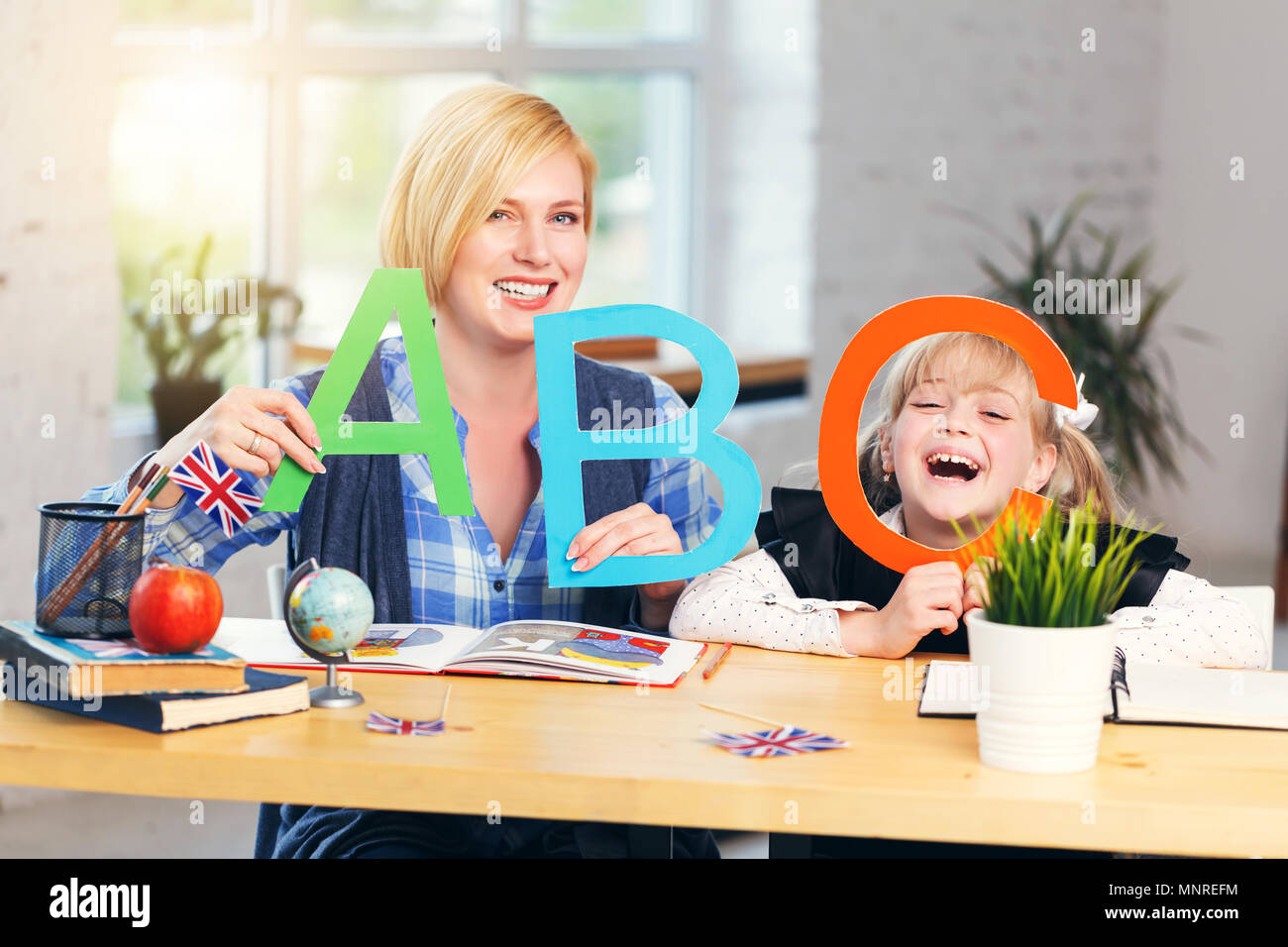 Intelligent smiling blonde English educator plays letters and words with kid school girl, table with books in light classroom with flowerpots - Stock Image