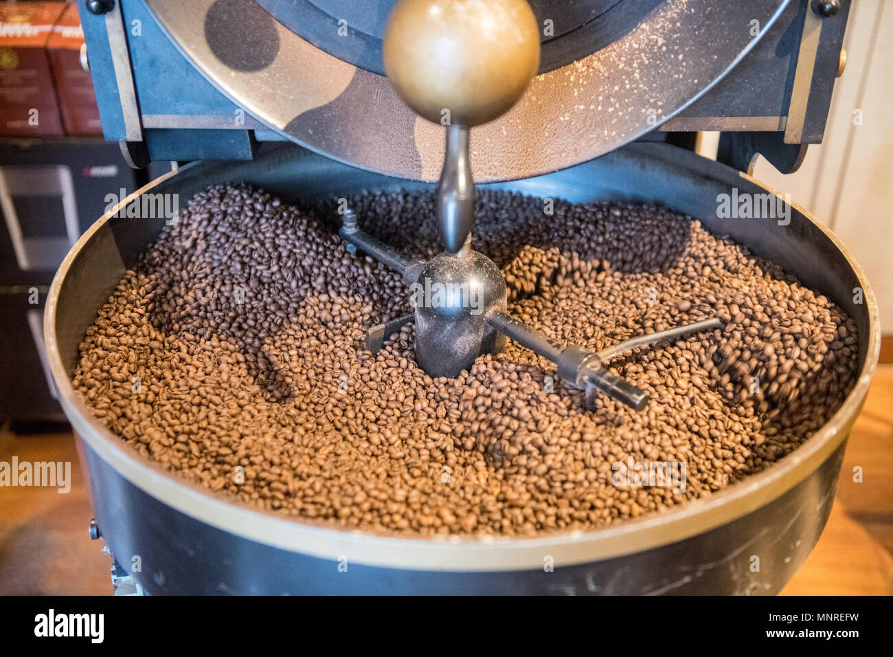 A mechanical arm of a machine slowly rotates freshly roasted coffee beans to cool them down, Istanbul, Turkey - Stock Image