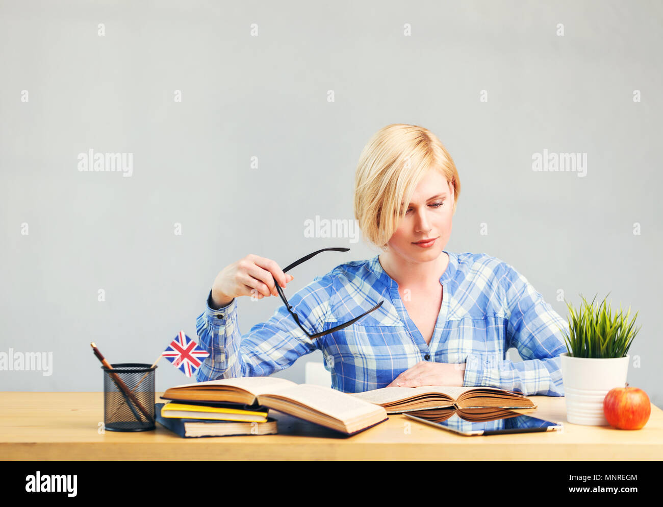 Smart female student, blonde woman holds eyeglasses in hand, studying English language on table with books, successful learning concept - Stock Image