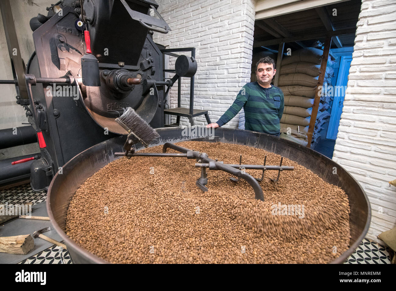 Adult male leans against coffee bean roaster as a mechanical arm slowly rotates freshly roasted coffee beans to cool them down, Istanbul, Turkey. - Stock Image