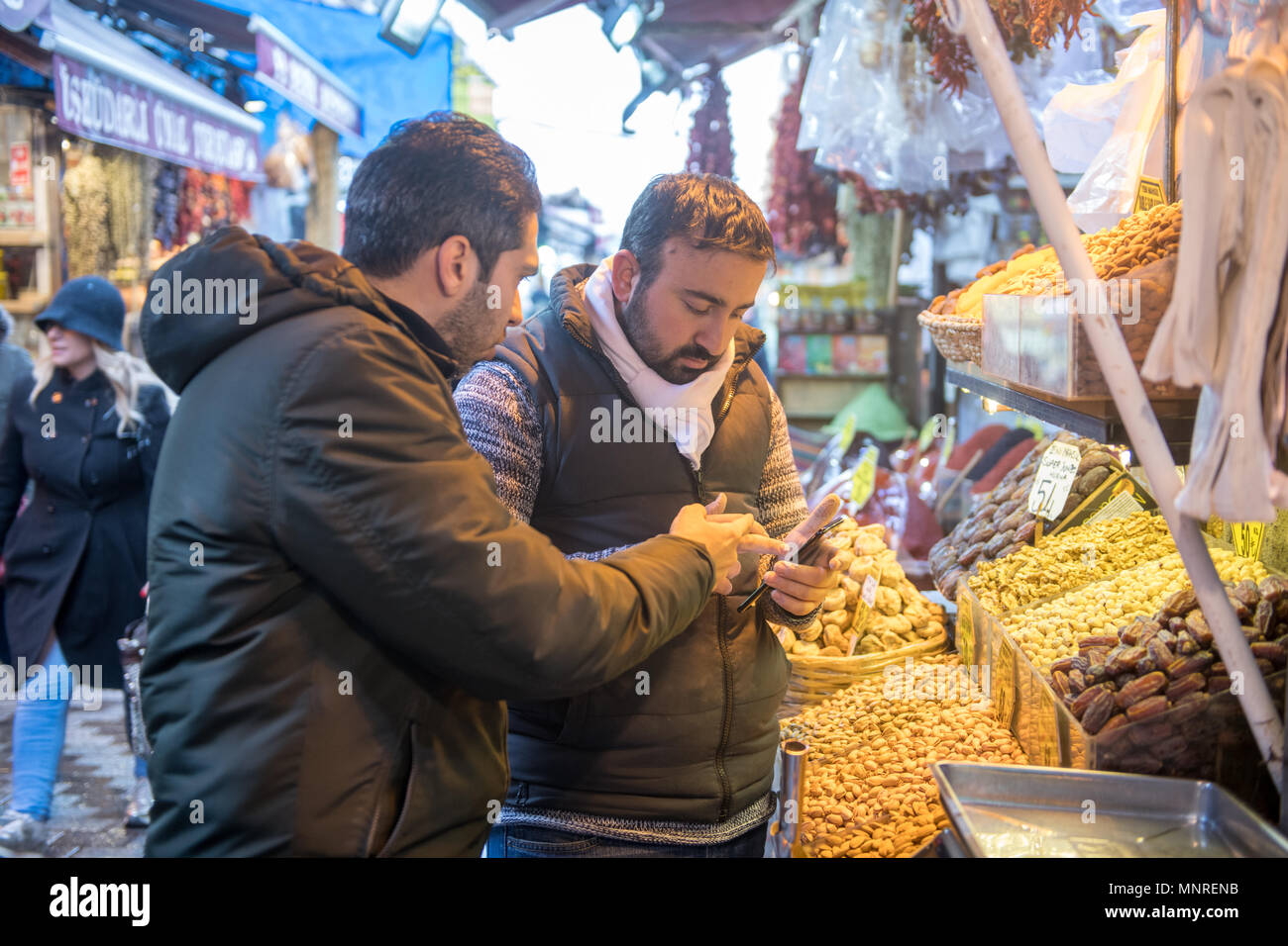 Two adult males point and look at cellphone together in front of market stall at outdoor marketplace, Istanbul, Turkey. - Stock Image