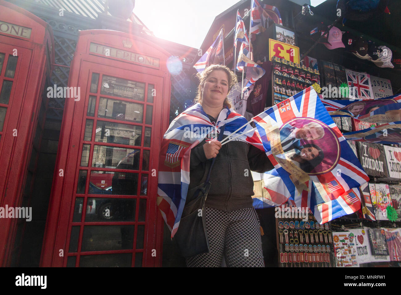 A woman waves a flag at a souvenir stall on Piccadilly in London to celebrate the marriage of Harry and Meghan Markle Stock Photo