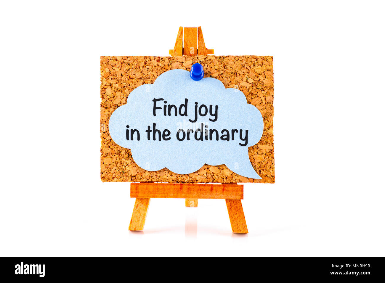 Blue speech bubble with phrase Find Joy in the Ordinary on corkboard on wooden easel. White background - Stock Image