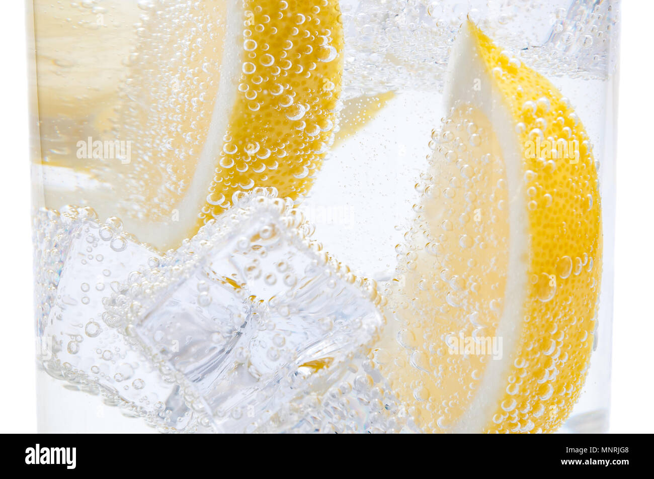 In a glass with cubes of melting ice slices of a juicy lemon. - Stock Image