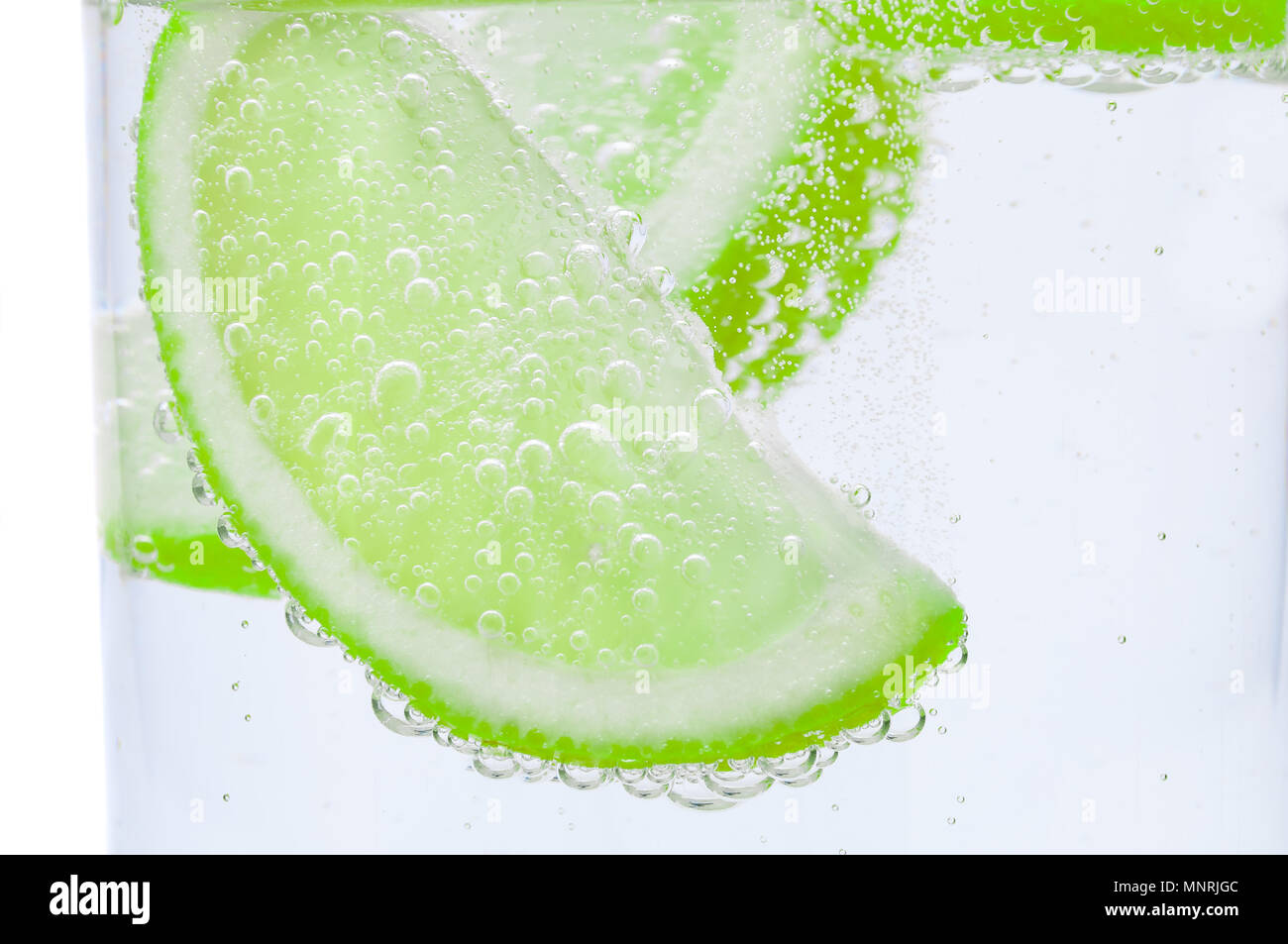 Pieces of fresh juicy lime sink into clear water. - Stock Image
