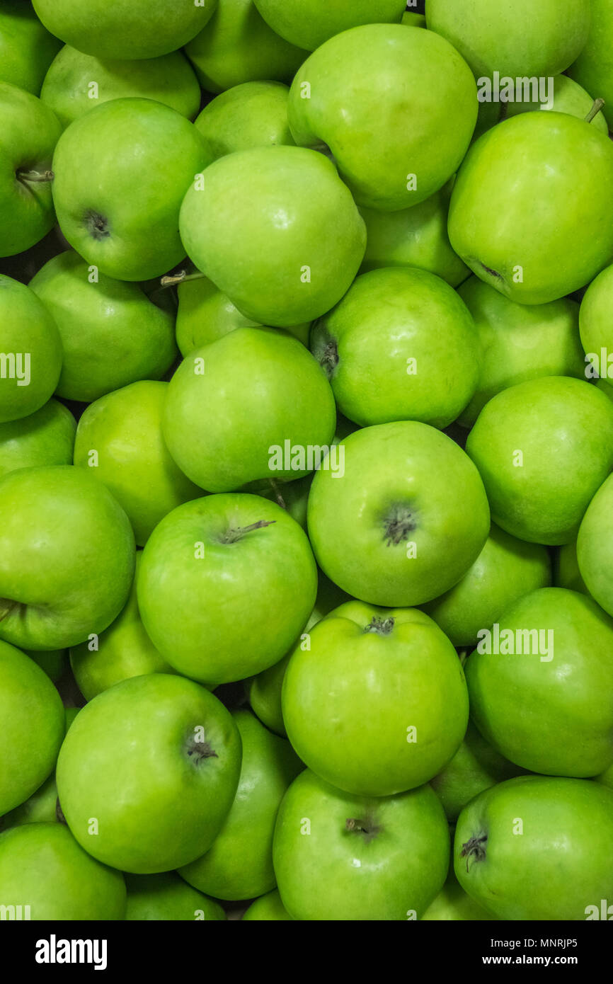 Green ripe juicy apples in a box on the market. Background - Stock Image