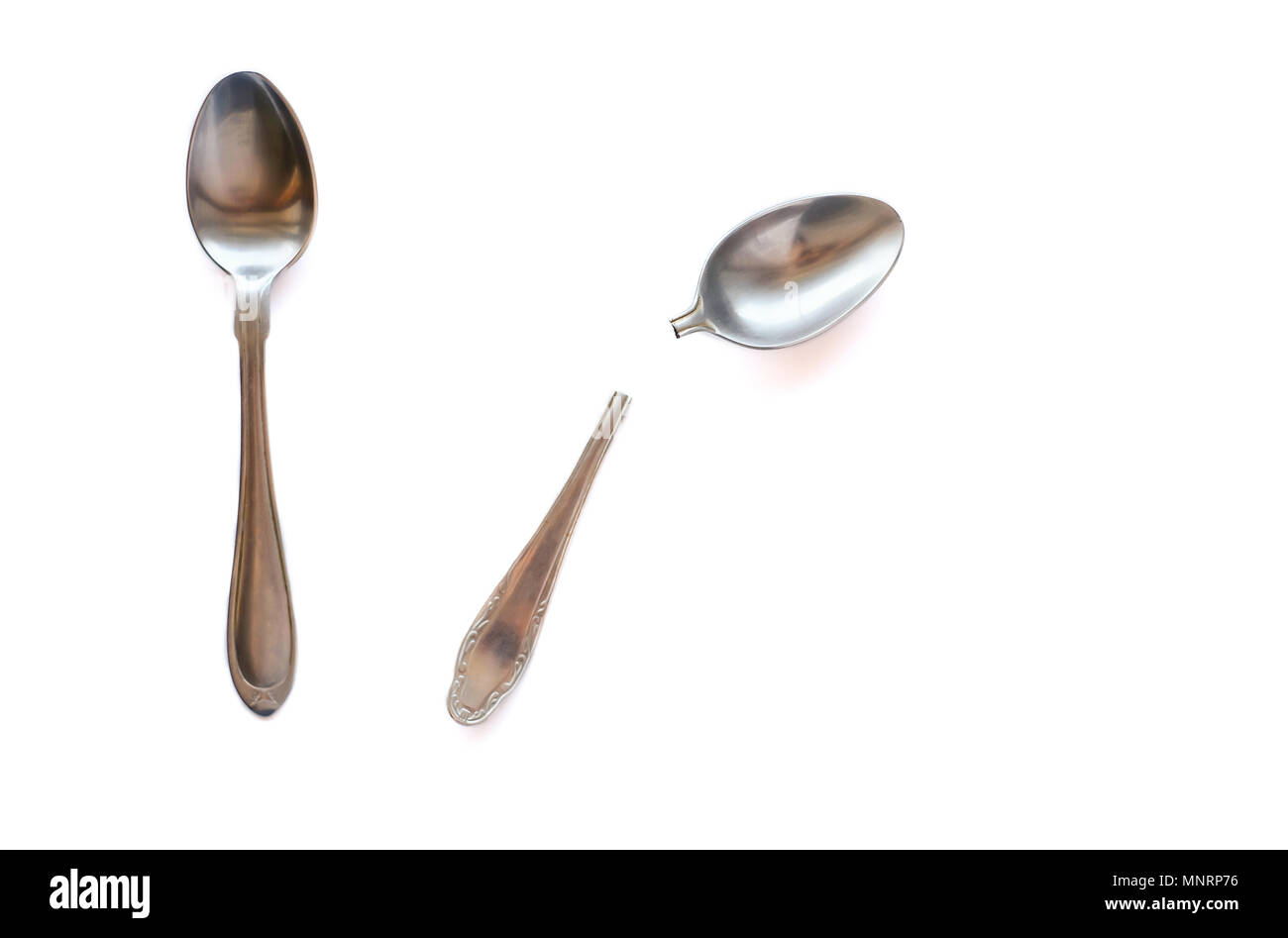 Two metal teaspoons - broken in half and serviceable on a white background. The concept of individuality in society and the family. - Stock Image