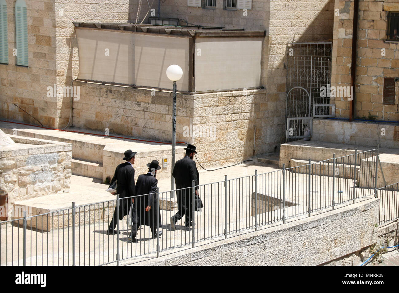 Jerusalem, Israel - May 16, 2018: Three Orthodox Jews walk through the Old City of Jerusalem, Israel. - Stock Image