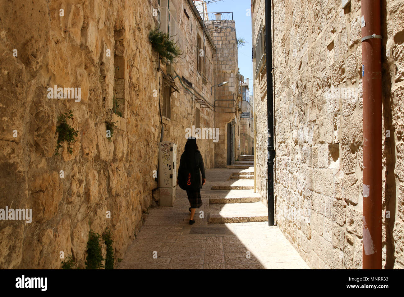 Jerusalem, Israel - May 16, 2018: A woman dressed in black walks in the midday sun through the old city of Jerusalem, Tel Aviv. - Stock Image