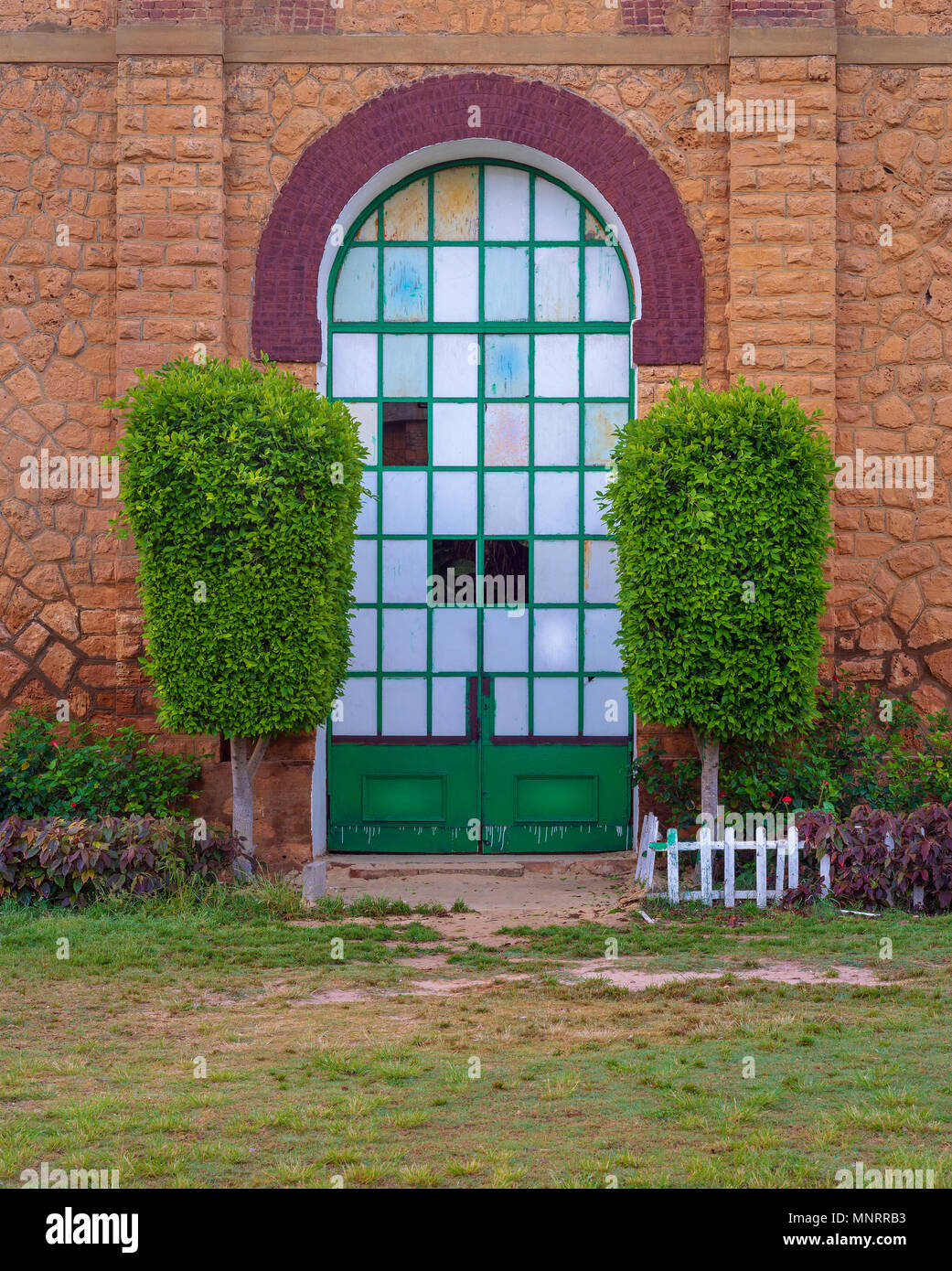 Closed grunge door with green metal grid framed by two green bushes in orange colored bricks stone wall in sunrise time at Montaza public park, Alexan - Stock Image