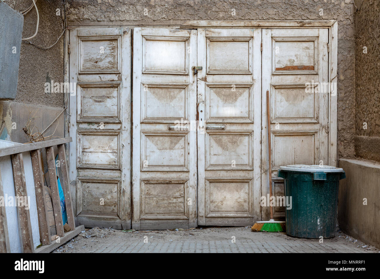 Wooden grunge weathered abandoned door painted in white, green trash can and ladder - Stock Image