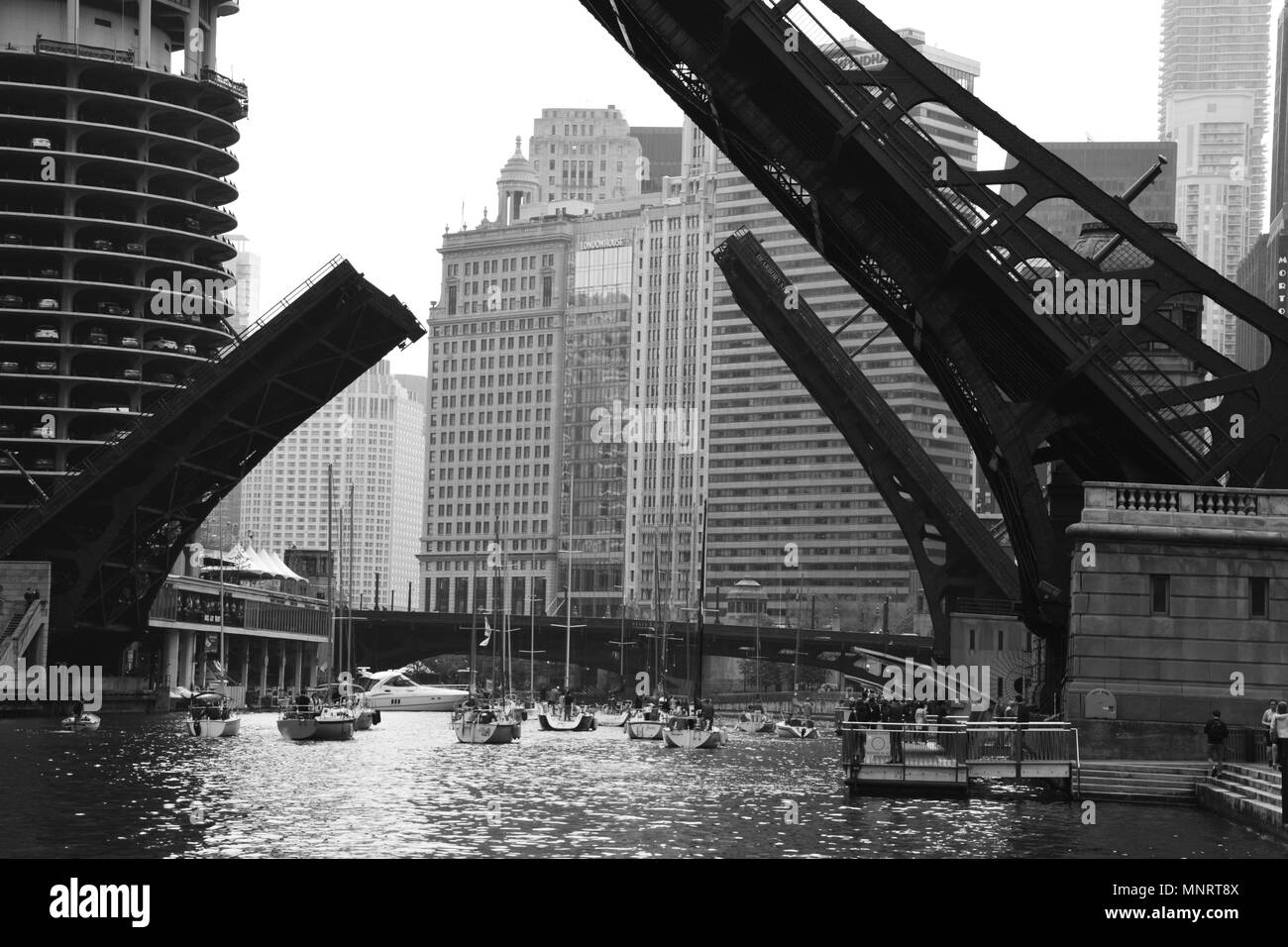 The downtown bridges in Chicago are raised to let sailboats pass during the spring boat run to Lake Michigan. - Stock Image