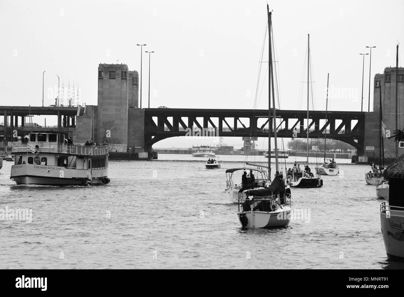 Sailboats approach the Lake Shore Drive bridge in Chicago during the spring boat run to Lake Michigan. - Stock Image