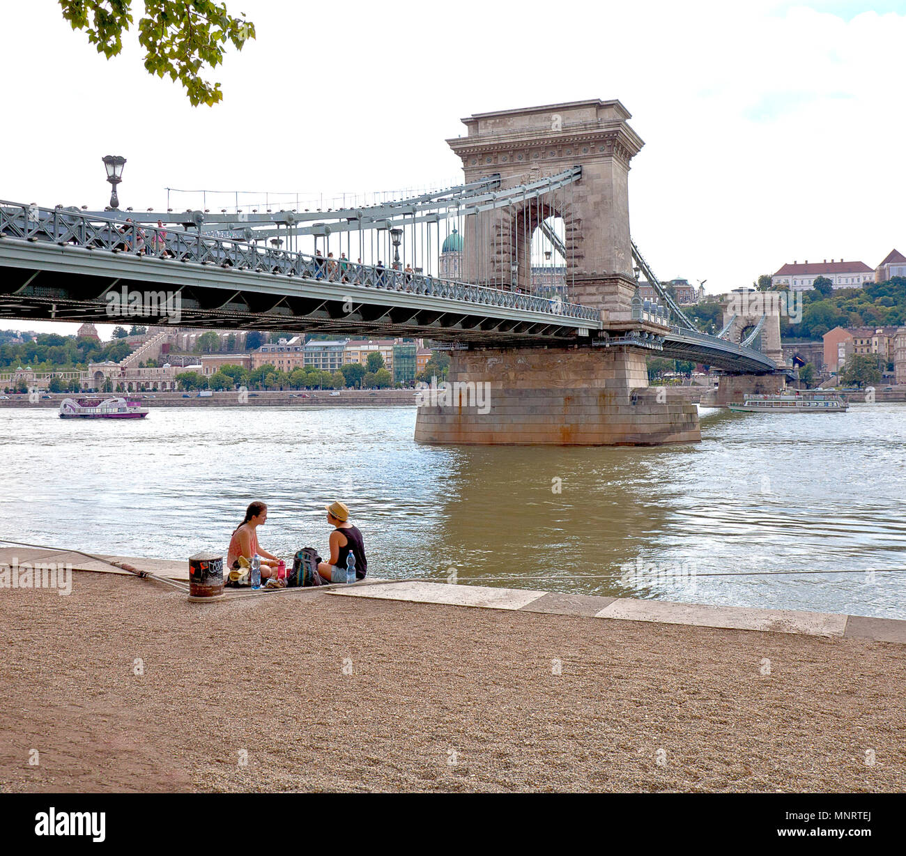 Two young girls picnic beside the Danube River near Dock 11 on the Pest side of the Elizabeth Bridge, Budapest, Hungary. - Stock Image