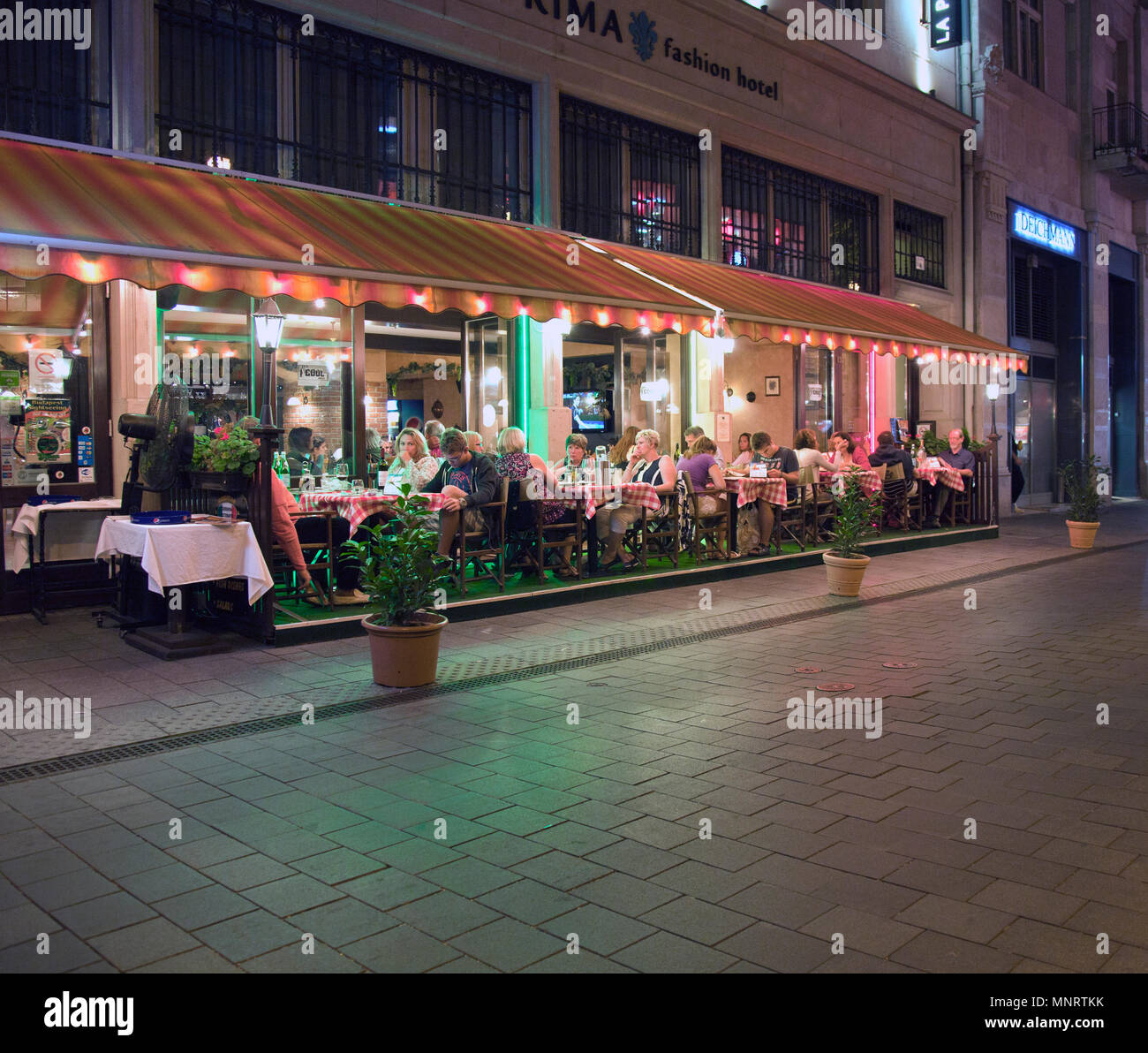 People enjoying dining out at a popular restaurant in the Vaci pedestrian area of downtown Pest, Budapest, Hungary. - Stock Image