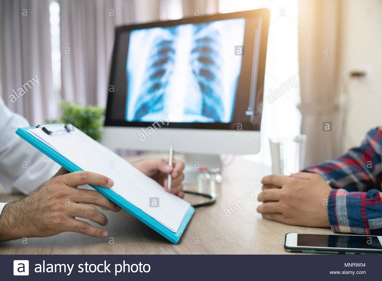 Close up of doctor filling up an application form while consulting patient Stock Photo