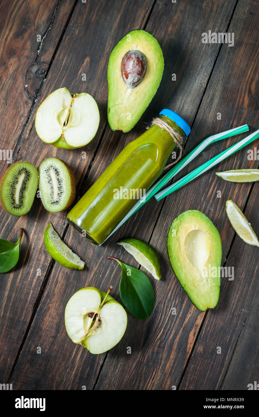 Green smoothie in bottl with avocado, apple and kiwi on white wooden background. - Stock Image