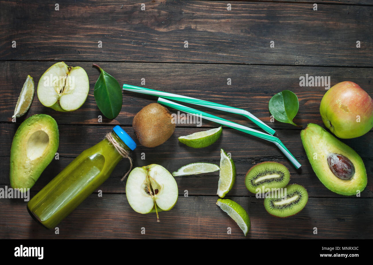 Green smoothie in bottl with avocado, apple and kiwi on white wooden background. Top view - Stock Image