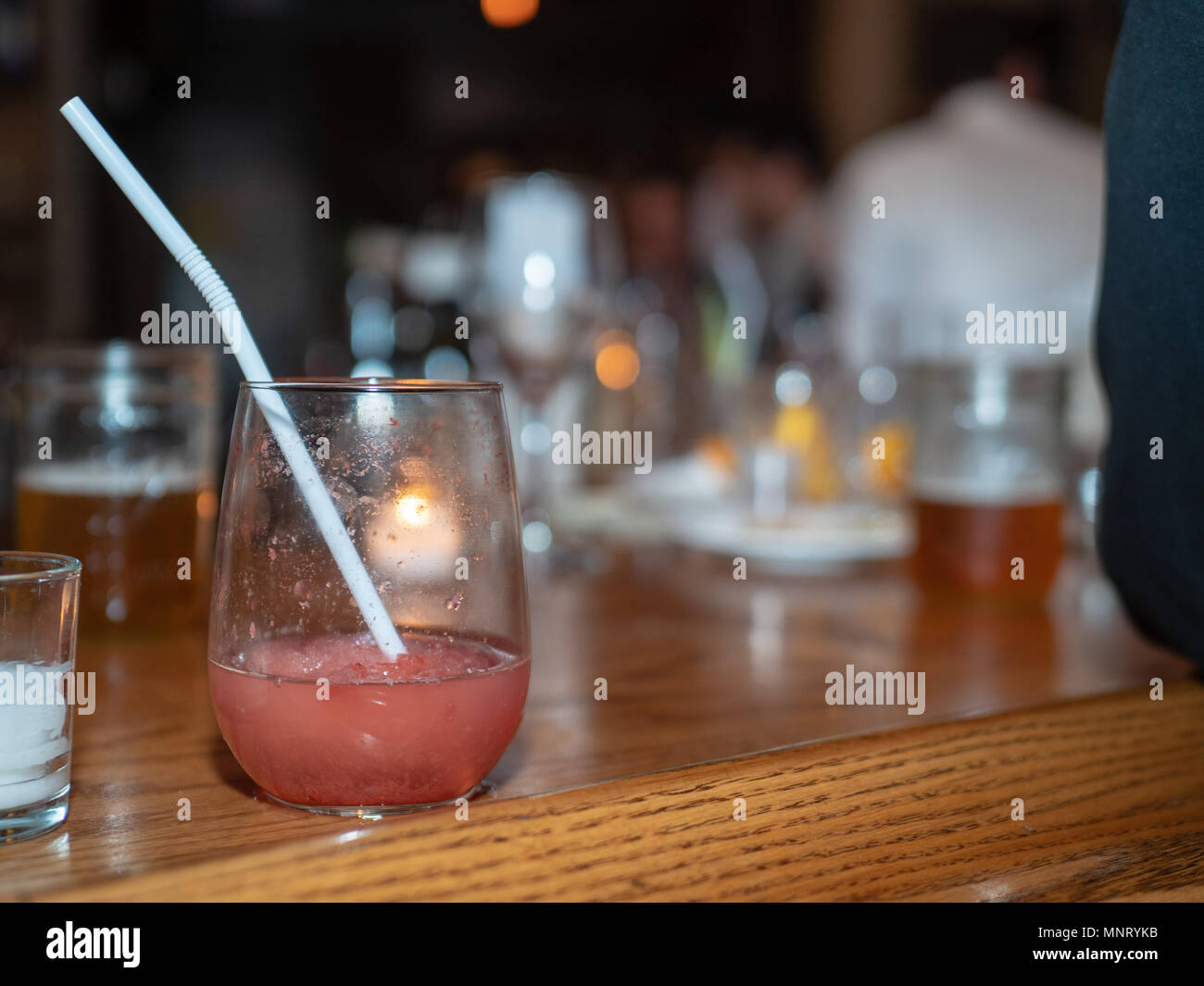 Fruity alcohol drink sitting on a busy bar with commotion all around - Stock Image