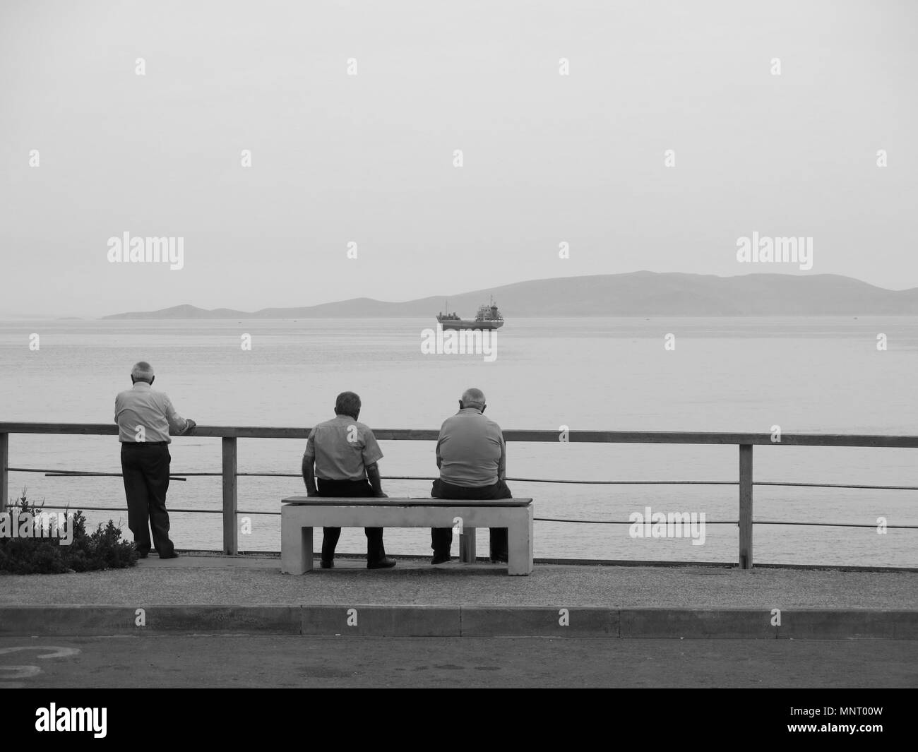 Elderly people looking at a ship from the promenade - Stock Image