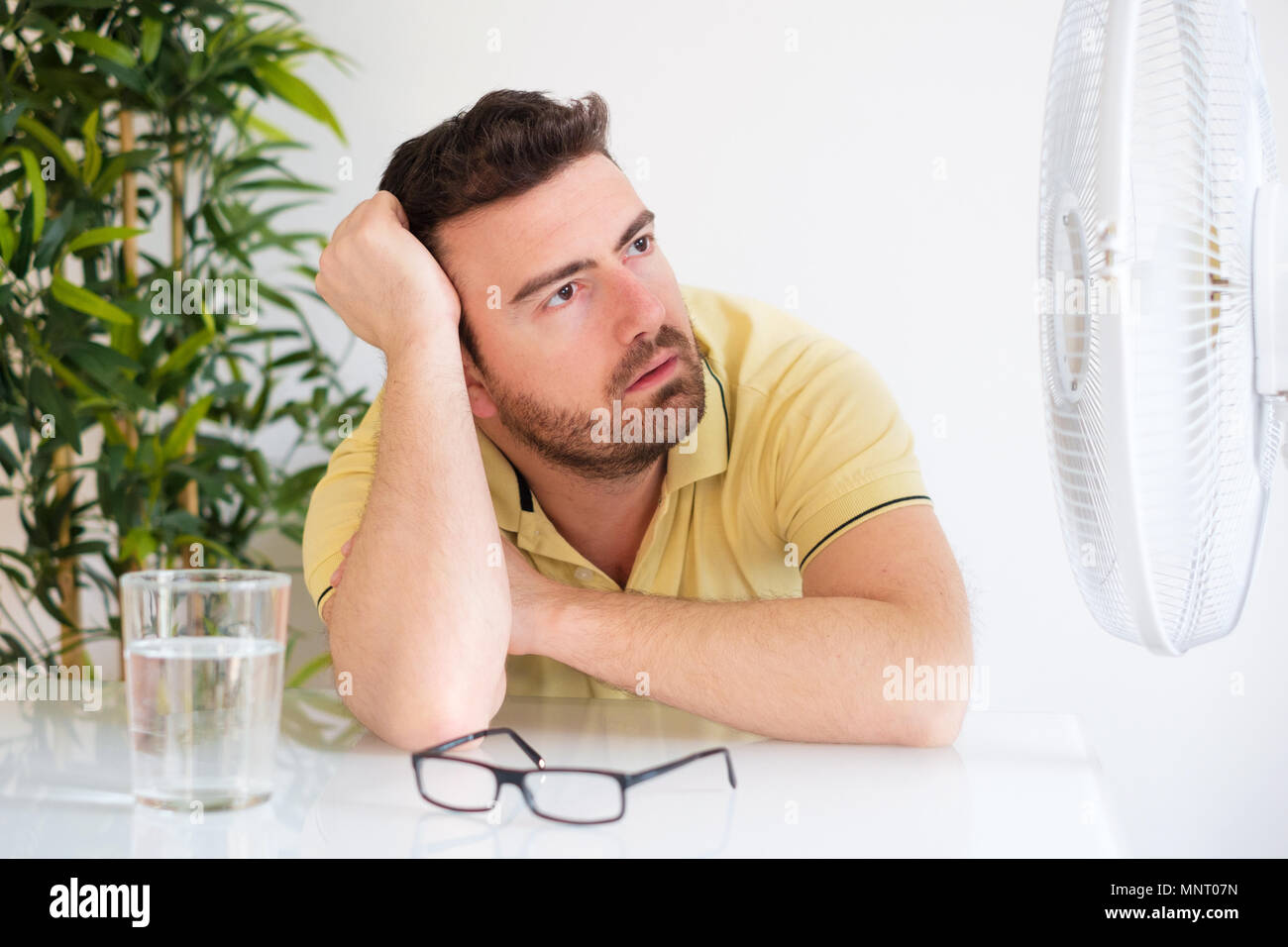 Young man sweating because summer heat haze - Stock Image