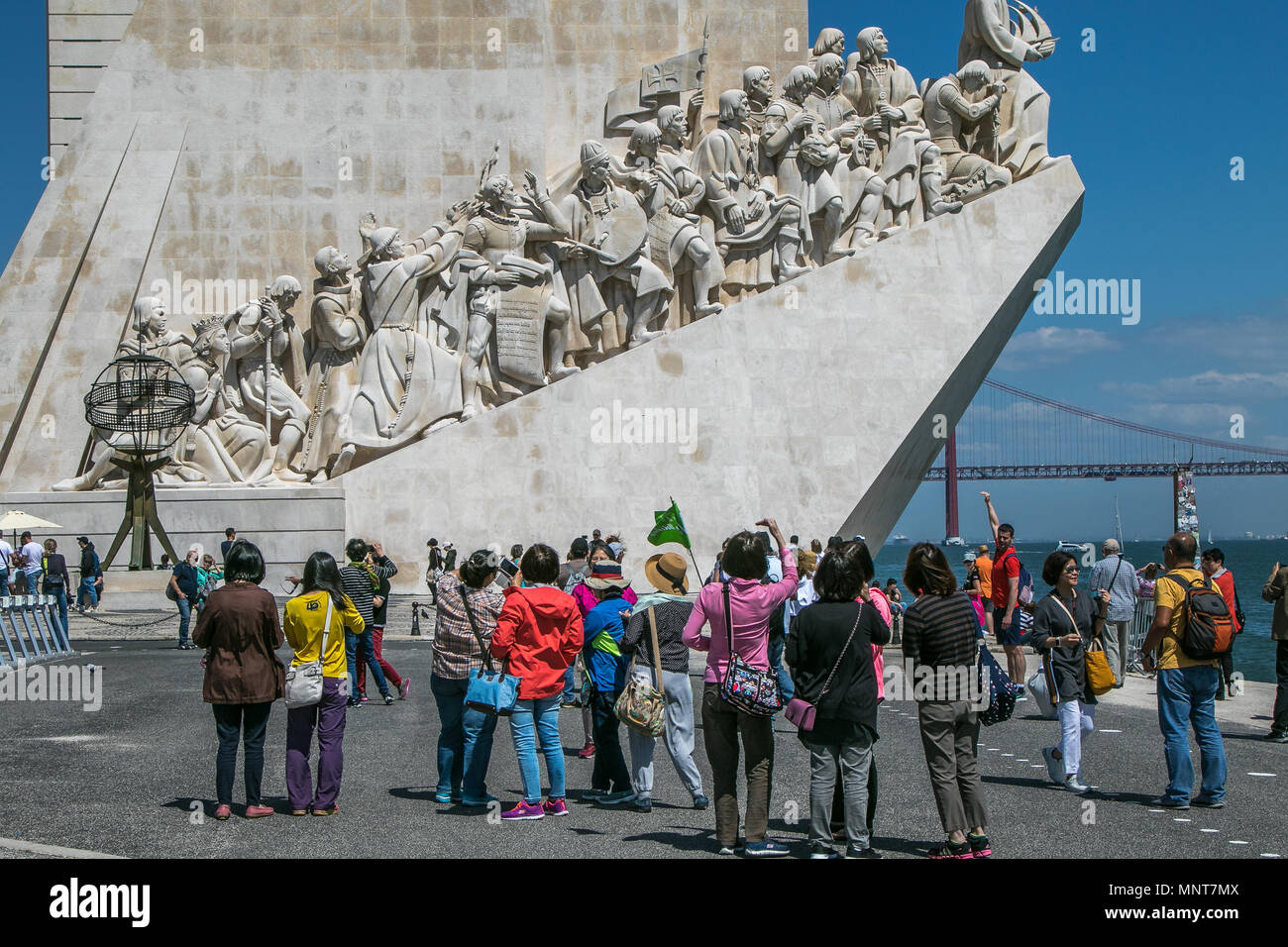 Asian tourists are taking pictures in front of the Monument to Discoveries in Belem, Lisbon, Portugal. - Stock Image