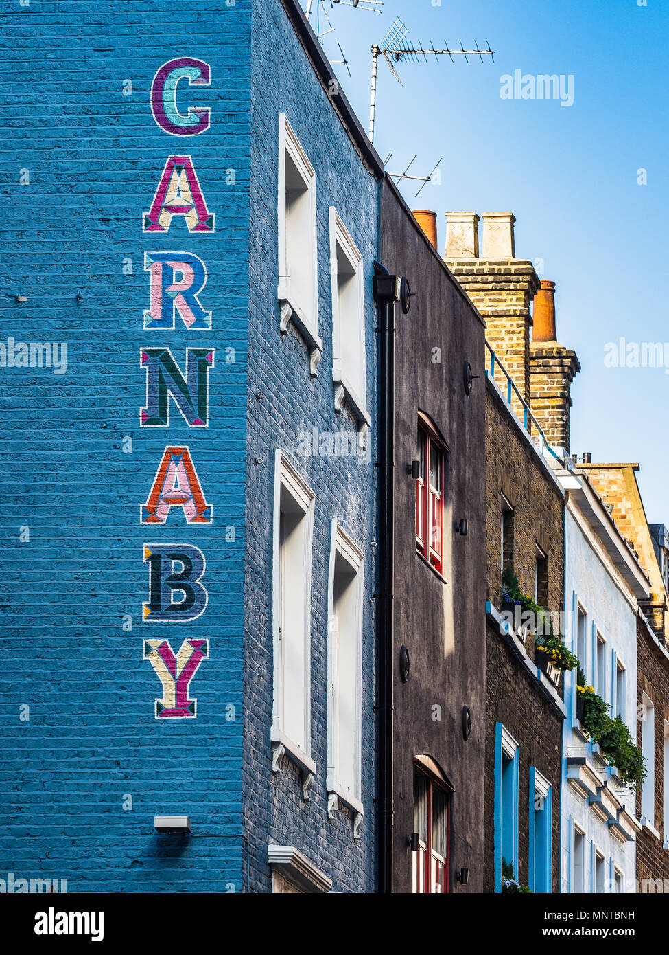 Carnaby Street London - painted sign on the side of a building in London's Soho district, Carnaby is famous as the heart of swinging London in the 60s - Stock Image