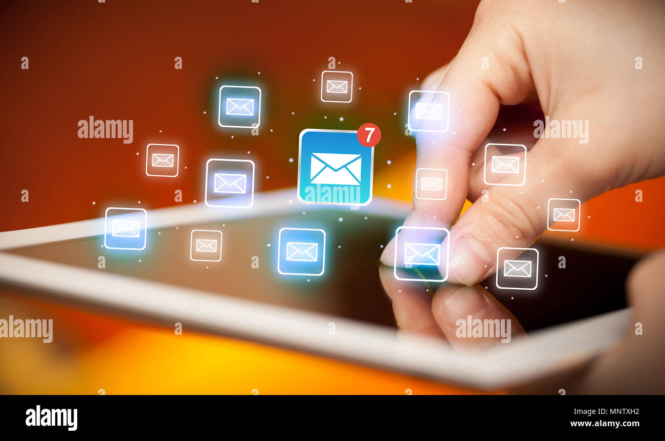 Female hands touching tablet with e-mail icons  - Stock Image