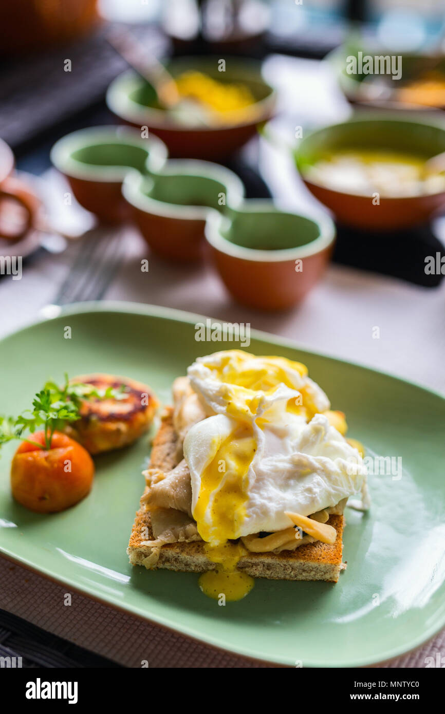 Breakfast table filled with assorted food.  Poached eggs,  Sri lankan curry and tea - Stock Image
