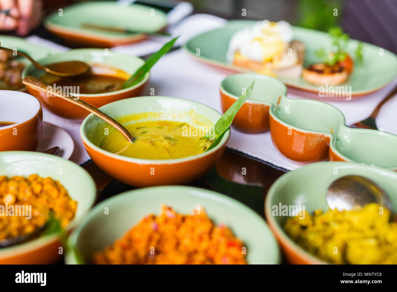 Variety of Sri Lankan curry in bowls on table - Stock Image