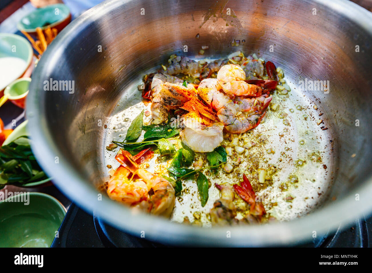 Preparation of traditional Sri Lankan curry dish with shrimps at cooking class - Stock Image