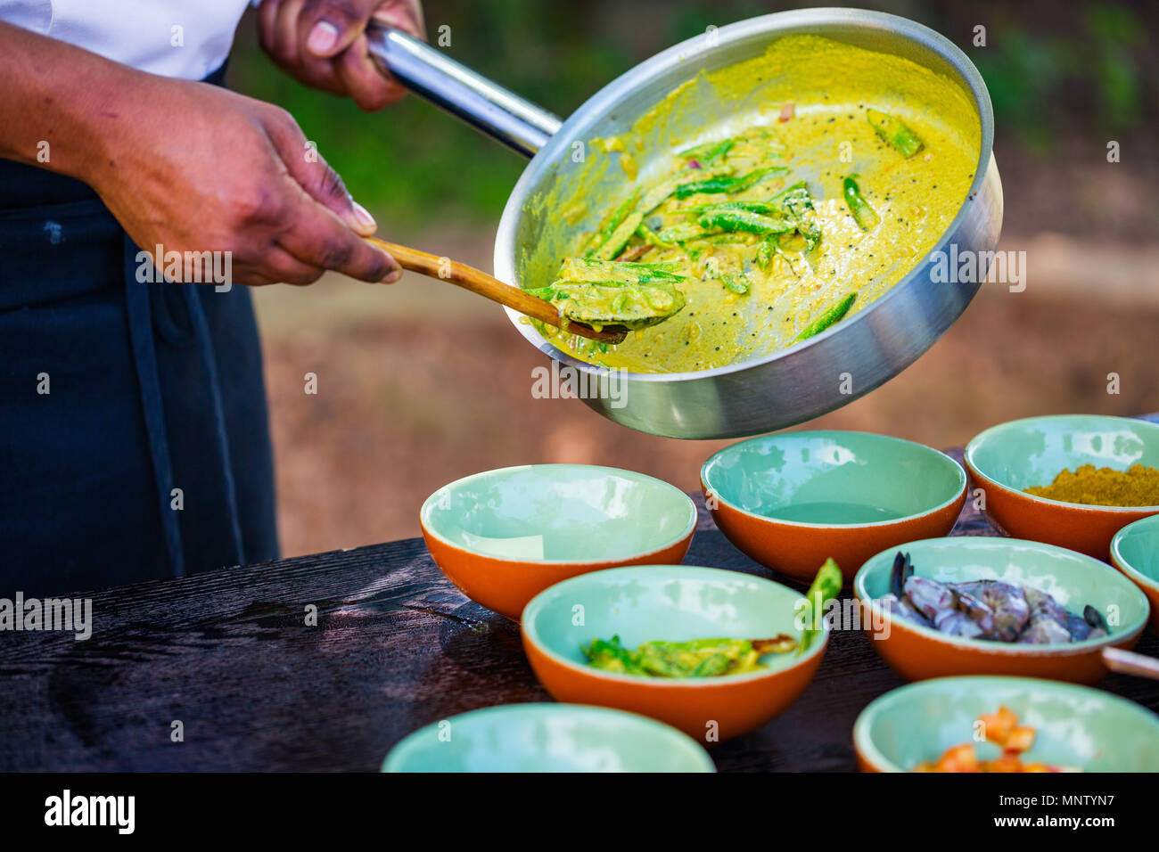 Chef making traditional Sri Lankan curry dish at cooking class - Stock Image