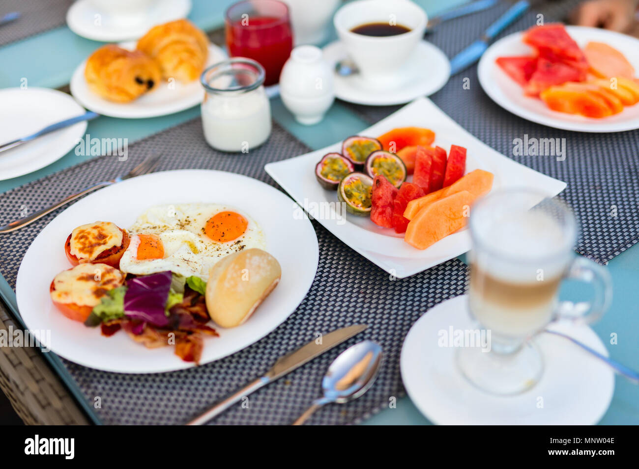 Delicious breakfast with fried eggs,  bacon,  vegetables and fruits - Stock Image