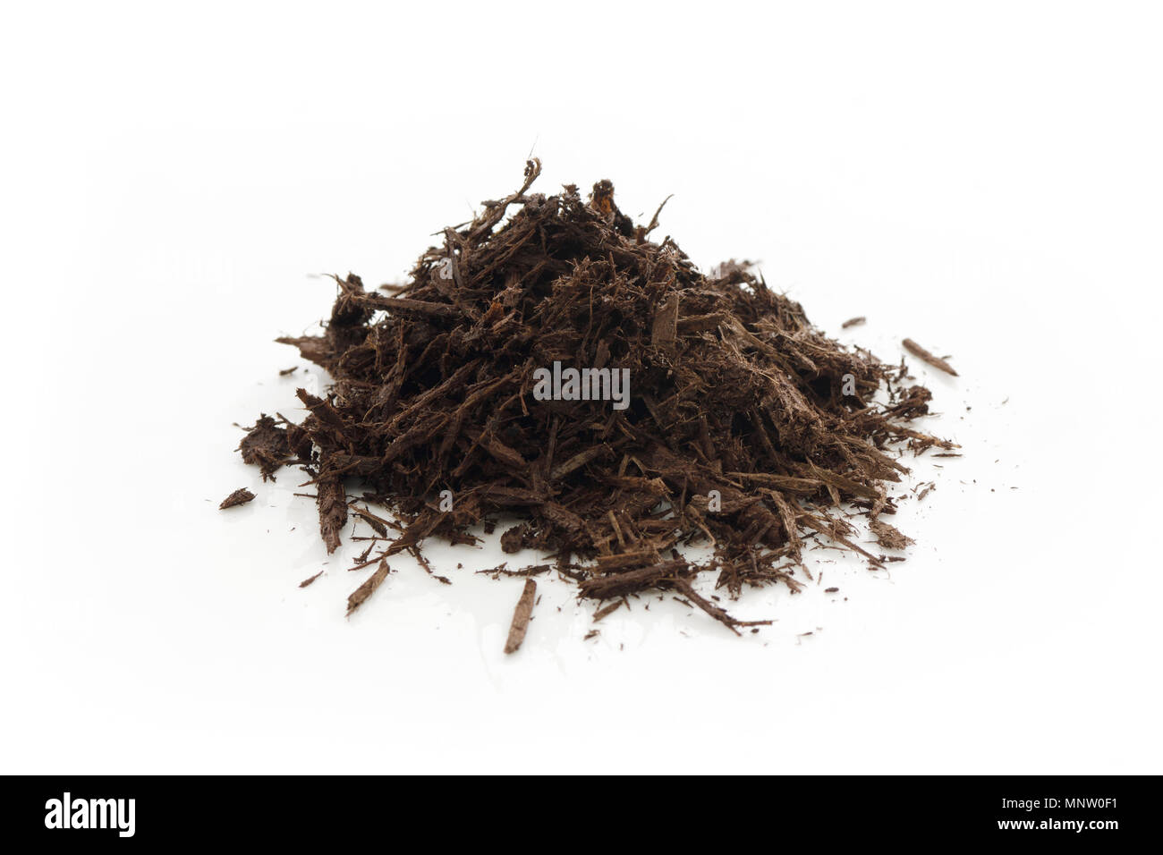 Tree bark and wood chips mulch used in horticulture and gardening. Closeup of an isolated cone pile on white studio background. - Stock Image