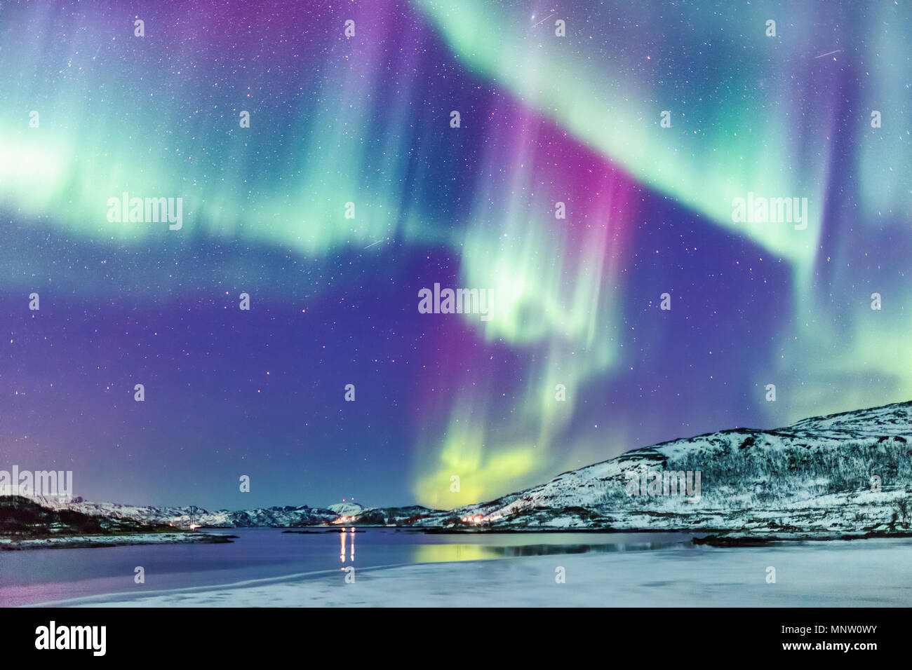 Incredible Northern lights Aurora Borealis activity above the coast in Norway Stock Photo