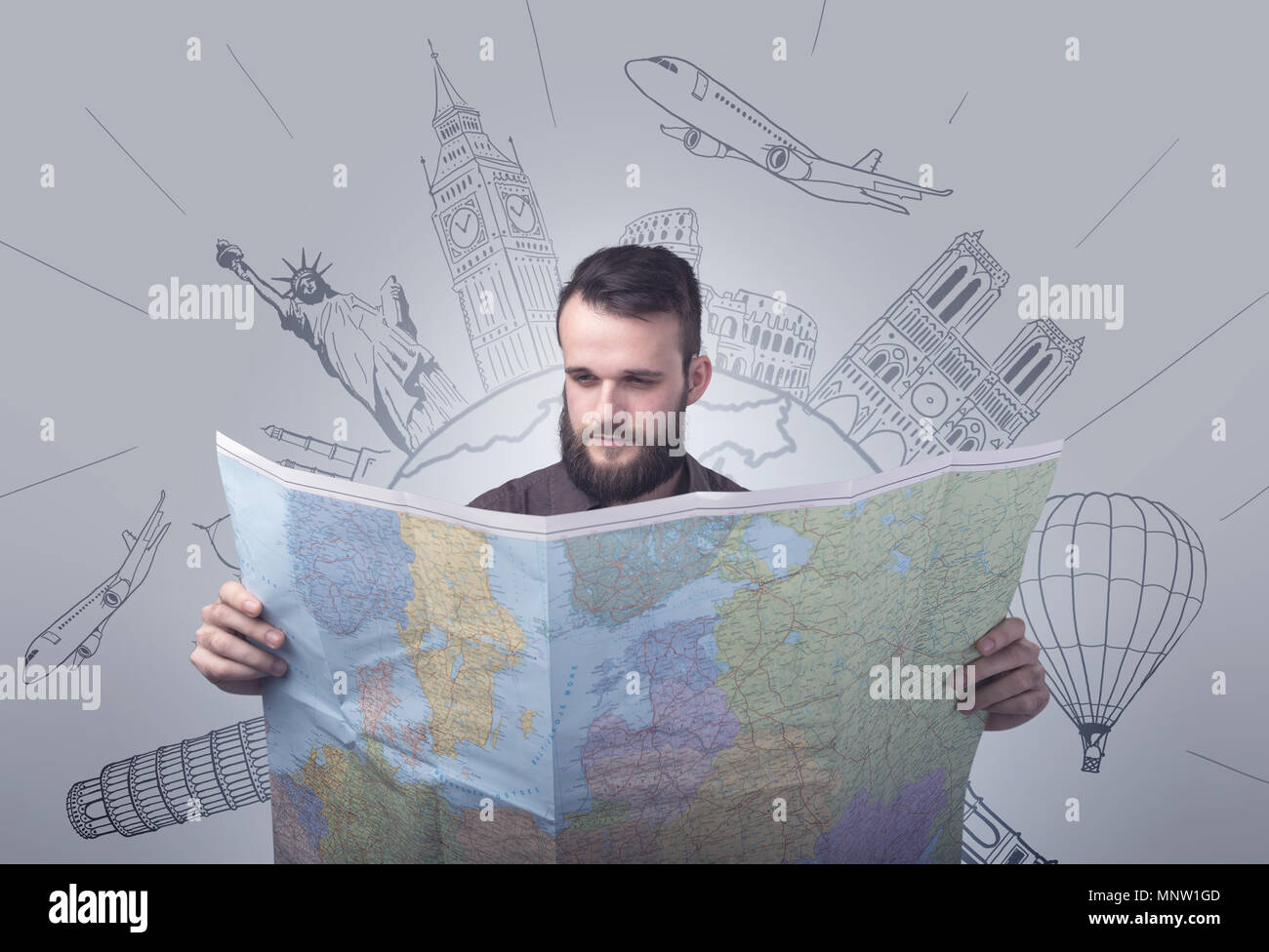 Handsome young man holding a map with famous sightseeing destinations above his head - Stock Image