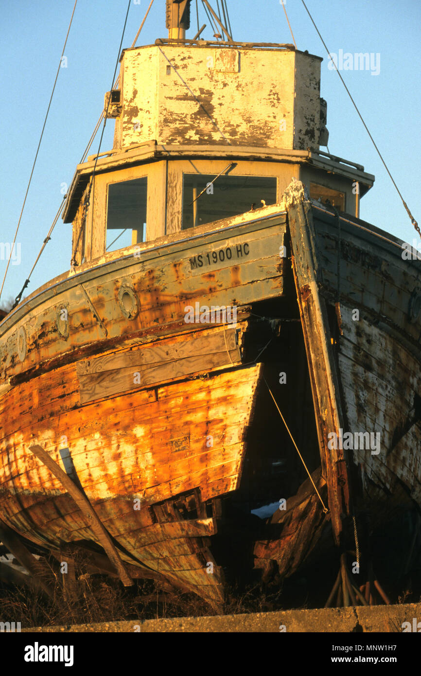 MThe setting sun illuminates an abandoned boat ashore in Onset, Massachusetts, USAultiple values - Stock Image