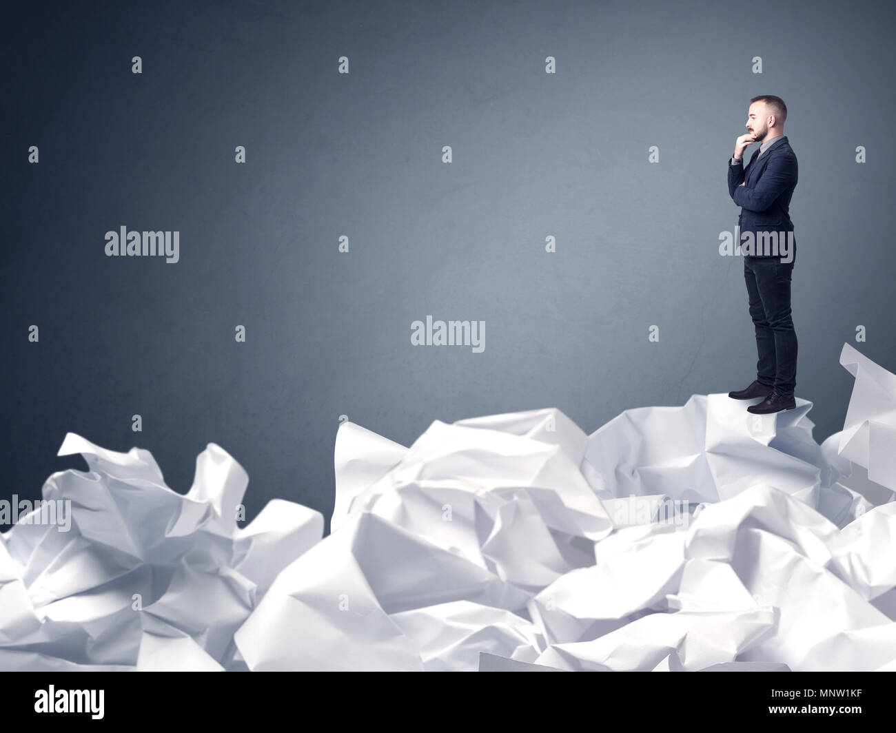 Thoughtful young businessman standing on a pile of crumpled paper with a blueish grey background - Stock Image