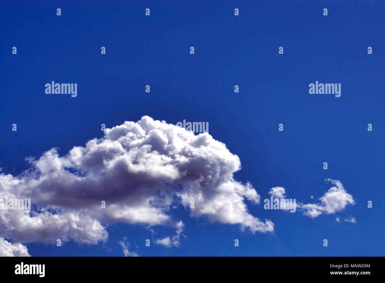 White fluffy clouds in the vast blue sky. Predominantly sky, copy space. Abstract nature background. Close-up. - Stock Image