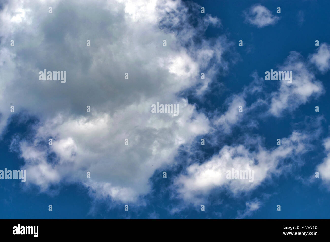 White fluffy clouds in the vast blue sky. Abstract nature background. Close-up. - Stock Image