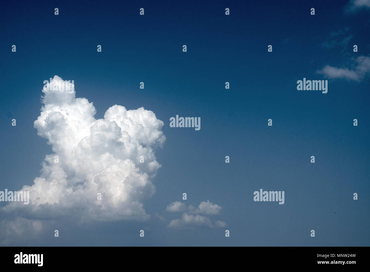 White fluffy clouds in the vast blue sky. Predominantly sky, copy space. Abstract nature background. Copy space for text. Close-up. - Stock Image