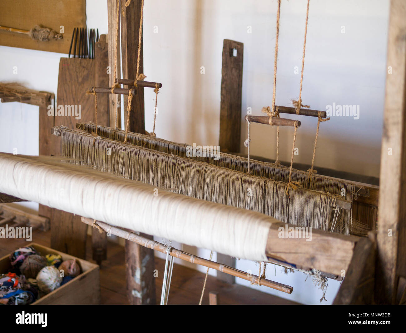 Detail of a Cloth making Loom: A hand operated wooden loom on display in the museum. - Stock Image