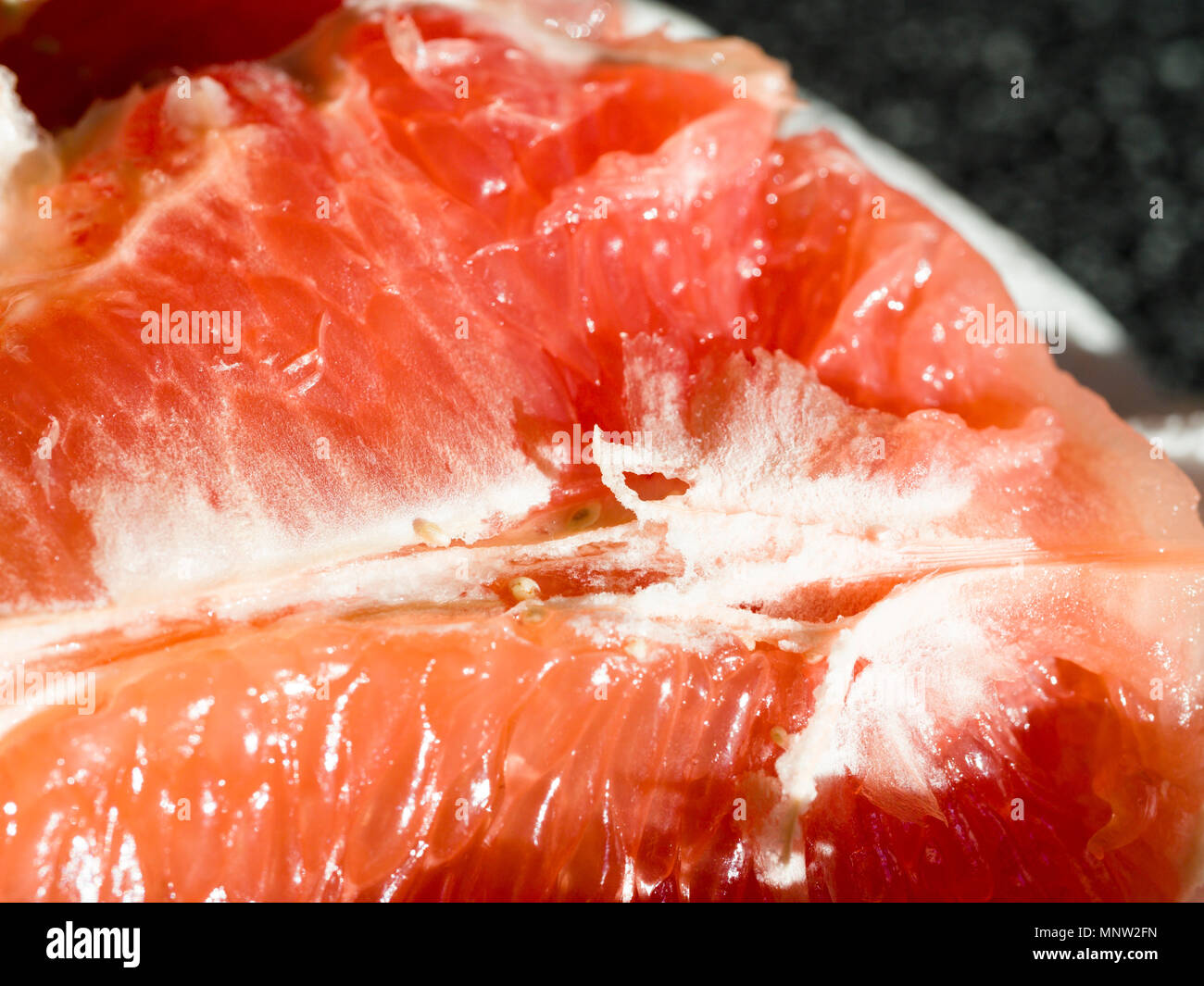 Closeup of Ruby Red Grapefruit segments: A deep red grapefruit opened and ready to eat shines in the early morning sun. - Stock Image