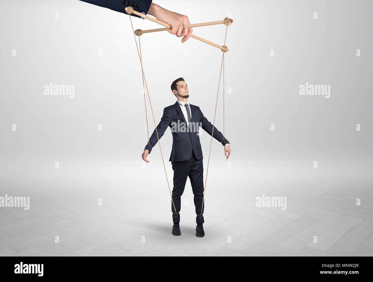 Puppet businessman in an empty room leaded by a huge hand  - Stock Image
